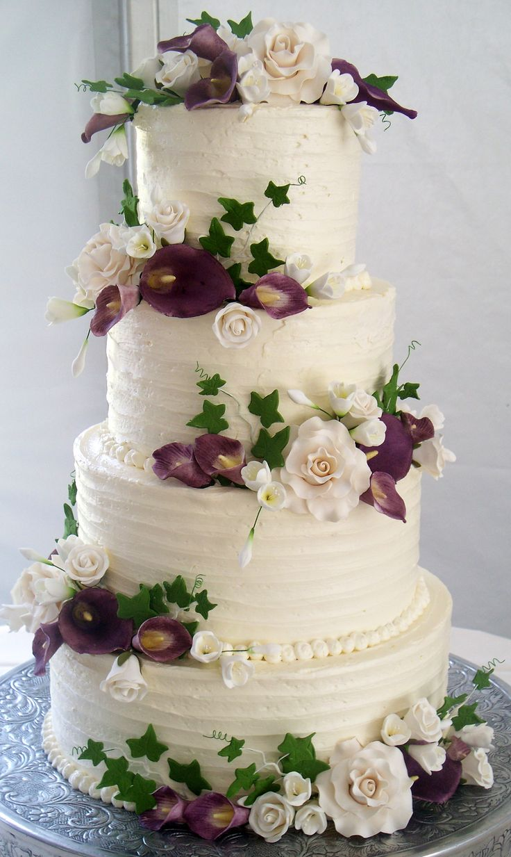 4 tier wedding cake, textured buttercream and coordinating flowers.