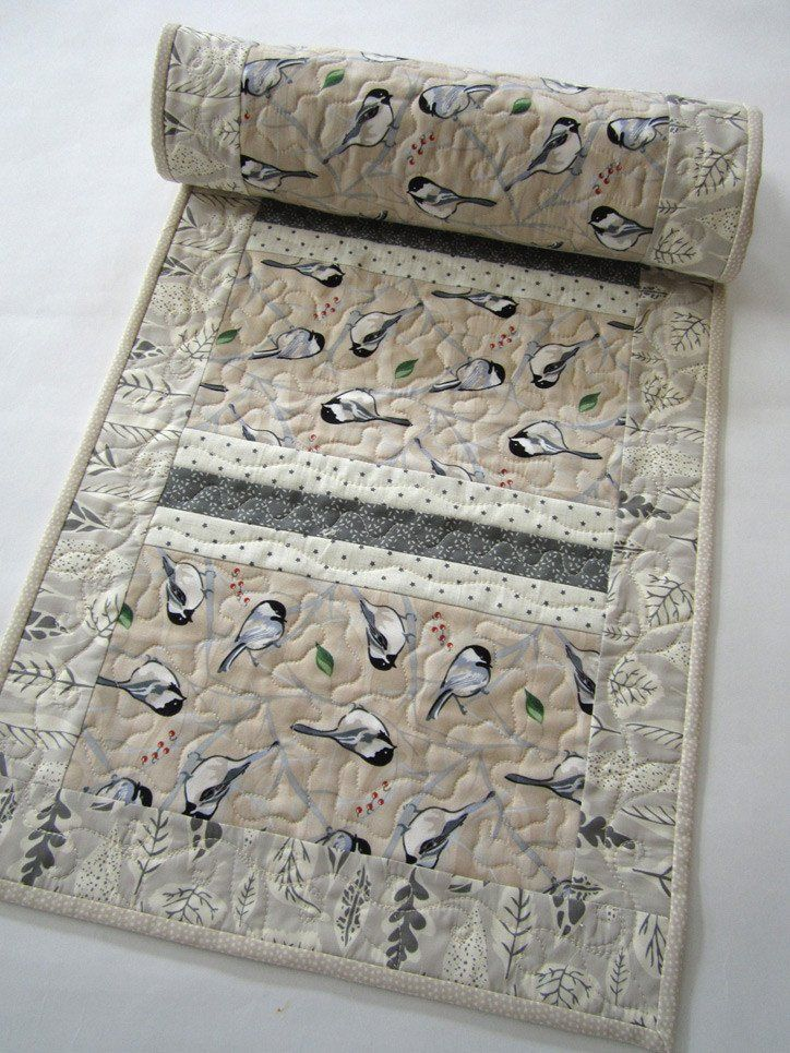 This table runner has birds in the main fabric with neutral fabrics throughout. A beautiful runner that would look nice in any room. There is a mixture of gray, beige and white in the fabrics. This ta