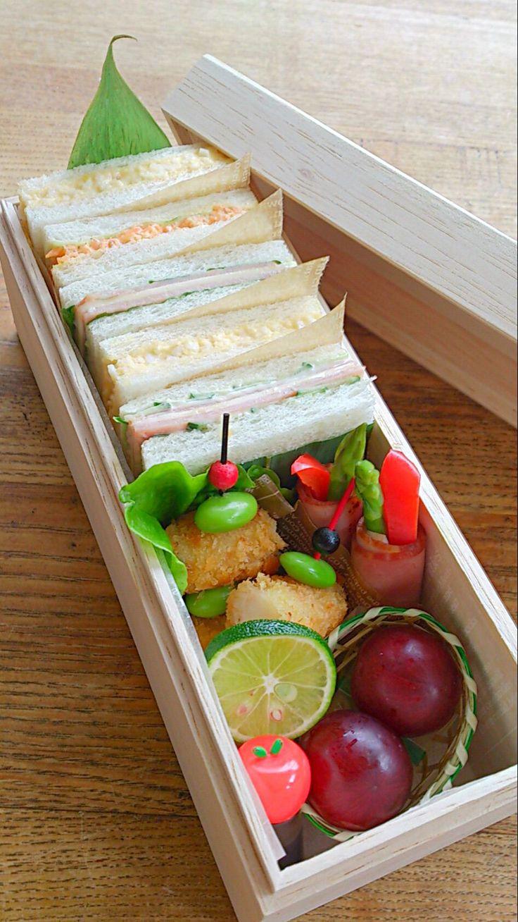10_Mayumi_Japan 4種のサンドイッチ(卵サンド・人参の胡麻マヨネーズドレッシング・ハムチーズ&レタス・ハムチーズ&キュウリ)、ベーコンとパプリカのベーコン巻き、海老フライ、葡萄 中学生の娘の為に作りました。女の子が食べやすいサイズ&取りやすい様にサンドイッチの間にワックスペーパーを挟んでいます。