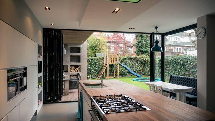 Aanbouw en renovatie van 2-onder-1-kapper met ruime woonkeuken met kookeiland, gietvloer en luxe aluminium vouwschuifpui: moderne Keuken door Joep van Os Architectenbureau