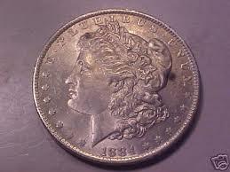 """DAMA DE TRÉBOLES. Dolar Morgan de plata, acuñado en 1884. La moneda que utilizaban nuestros personajes. En el anverso figuraba la imagen de Miss Liberty, la libertad.   Y en el reverso, el águila con las flechas y la rama de olivo, circundada por la leyenda """"En Dios confiamos""""."""