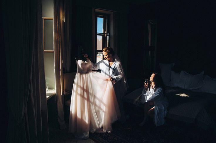 Невеста держит в руках своё платье