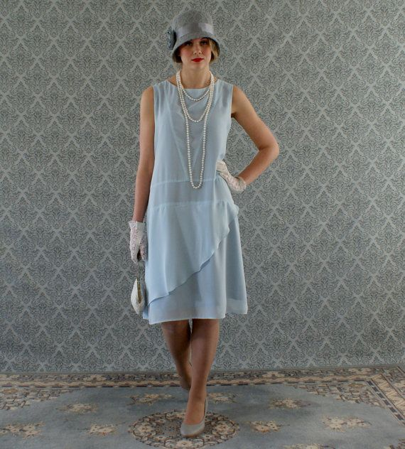 This sweet light blue flapper dress is a real darling! It is made of chiffon fabric which is very soft to the touch and drapes beautifully. We love the skirt detail of the ruffled part which goes from one side of the dress all the way from the front, around the back and meets again on the same side. A small rolled hem is used for the ruffled part so that it will flow and drape freely. The front of the bodice has lovely V shape seams adding nice details to the streamlined design of the dress…