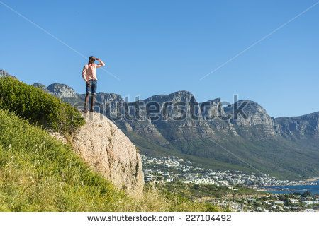 http://www.shutterstock.com/pic-227104492/stock-photo-african-black-man-standing-on-a-high-rock-overlooking-cape-town-as-he-points-and-scouts-the-blue.html?src=WuffEuvvGWj02MQSGcnIHQ-1-10 African Black Man, Standing On A High Rock Overlooking Cape Town As He Points And Scouts The Blue Sky, Ocean And Mountains On A Sunny Summers Day Stock Photo 227104492 : Shutterstock