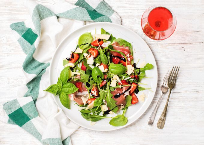 #Prosciutto & strawberry salad  Summer arugula prosciutto and strawberry salad with glass of rose wine over white painted wooden background top view horizontal composition
