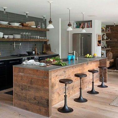 Un esprit industriel brocanté règne dans cette cuisine. Le plan de travail en acier se conjugue à merveille avec la structure en bois brut qui le soutient ainsi que les tabourets chinés en métal.  Du côté des fourneaux, la crédence en carrelage gris et les meubles noirs apportent la touche industrielle moderne. Les étagères en bois brut au dessus de l'évier rajoutent un côté authentique et récup' à la pièce. La vaisselle blanche exposée sur ces dernières fait directement référence aux…