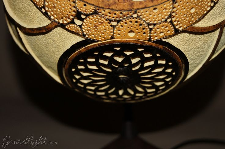 https://flic.kr/p/jDjAaK | Table lamp IX | Head of the lamp is made of Senegalese calabash. White parts are carved layer of the fruit which change the color to red/orange when the lamp is switched on. On the bottom of the lamp there's perforated closing part locked by magnets. The lamp was painted with wood oil and alcohol ink. Black parts are burnt calabash surface. The center element is genuine Baltic amber- ranked as the world's finest;  resin from the ancient trees dating back ~40…