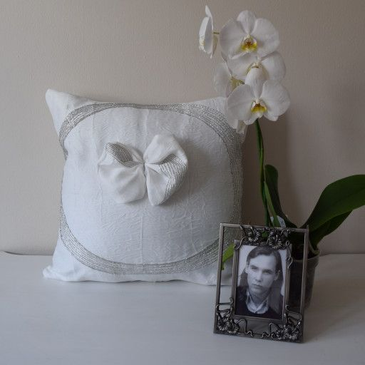 This elegant pillow cover is made of a white exclusive fabric, which is embroidered with silver lurex thread. The lurex threads formes circles on the edge of the pillow. In the center of the cushion I placed a bow from the same fabric. The back side of the cushion is the same fabric's plain version. It is an unique fabric, as there is a shinny organza application on the white decor textile. Some details: - it measures 18x18 inches and I have 1 pc of it - it has a hidden zipper at the bot...