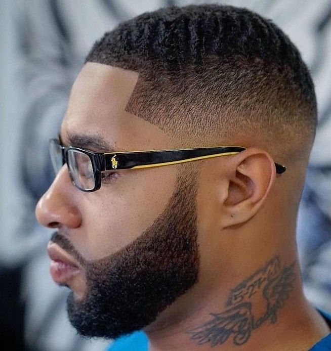 faded undercut, man with polo glasses with black and yellow frames, dark hair cropped very short on the side but kept longer on top, trimmed beard and mustache, tattoo on his neck
