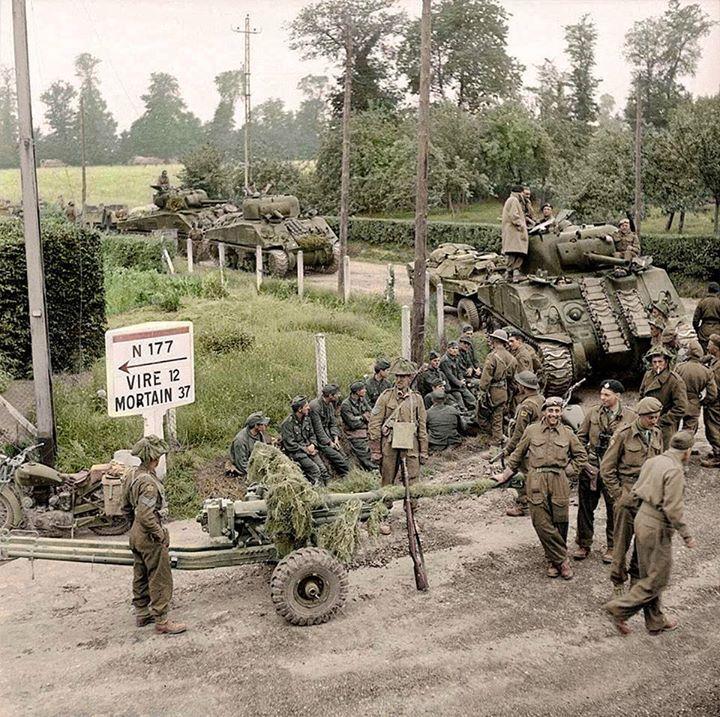 tanques britânicos Sherman e armas anti-tanque 6-PDR da 11ª Divisão Blindada, avançando através da vila de St Charles-de-Percy em Calvados, na Normandia, na estrada N 177 a Vire. 02 de agosto de 1944,