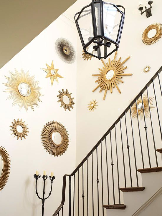 A collection of sunburst mirrors adds a dose of Art Deco sass to the staircase. - Traditional Home ®/ Photo: Tria Giovan / Design: Phillip Sides