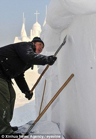A worker shapes a snow sculpture at Jingyuetan National Forest Park in Changchun, capital of northeast China's Jilin Province