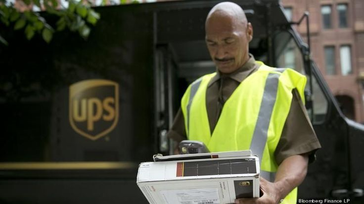 UPS parcel delivery vehicle and employee making a delivery