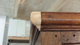 Hoek van de sierlijst van een eiken kast gerepareerd.