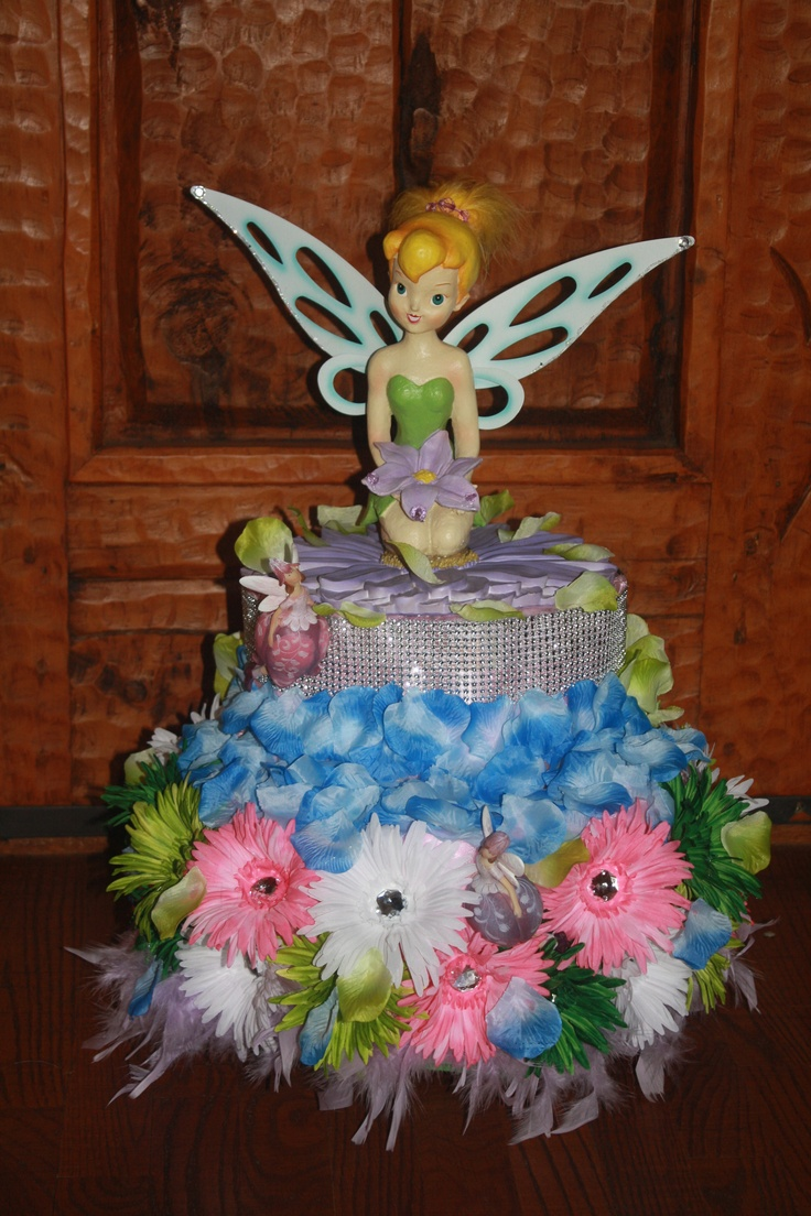 DIAPER CAKE TINKERBELL FOR SALE $65.00 INTERESTED   TEXT 903 279 3472  DIAPERS COVERED WITH ORGANZA TINKER BELL IS SITTING ON A LAVENDER FLOWER WITH HER FRIENDS (2) THE FAIRIES AROUND HER SHE HAS DIAMOND MESH ABOVE THE WATER SPRING (BLUE ROSES PETALS) GREEN ROSES PETALS FOR THE LEAF,COLORFUL SPIDER DAISIES WITH GLITTER STONE FOR HER GARDEN FINISHING WITH A  LAVENDER BOA AT THE BASE .p.s THE BACK OF THIS CAKE IS HAS PRETTY!!!