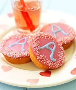Versierde roze koeken. Nodig: AH roze koeken (mini), Glazuur+stiften. Spikkels. Werkwijze: Verwarm het glazuur, besmeer de rand van de koek met het glazuur en dip het in het bakje spikkels. Schrijf met de glazuurstiften de eerste letter of leeftijd van het kind in het midden van de koek.