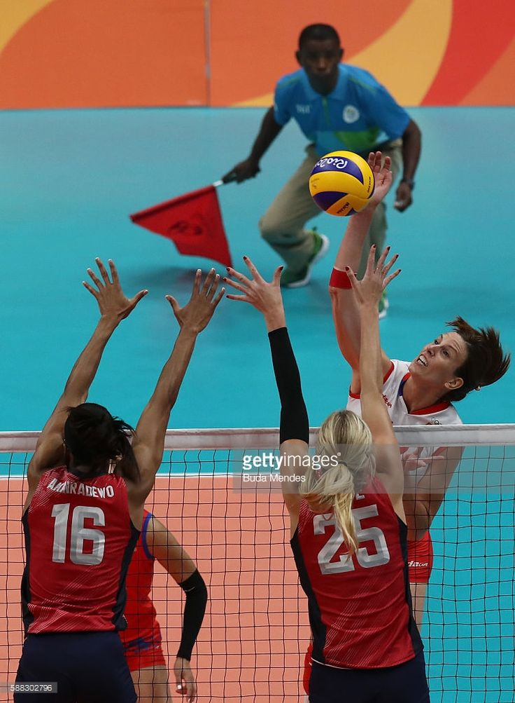 Jelena Nikolic #12 of Serbia spikes the ball against Foluke Akinradewo #16 and Karsta Lowe #25 during the women's qualifying volleyball match between the United States and Serbia on Day 5 of the Rio 2016 Olympic Games at the Maracanazinho on August 10, 2016 in Rio de Janeiro, Brazil.