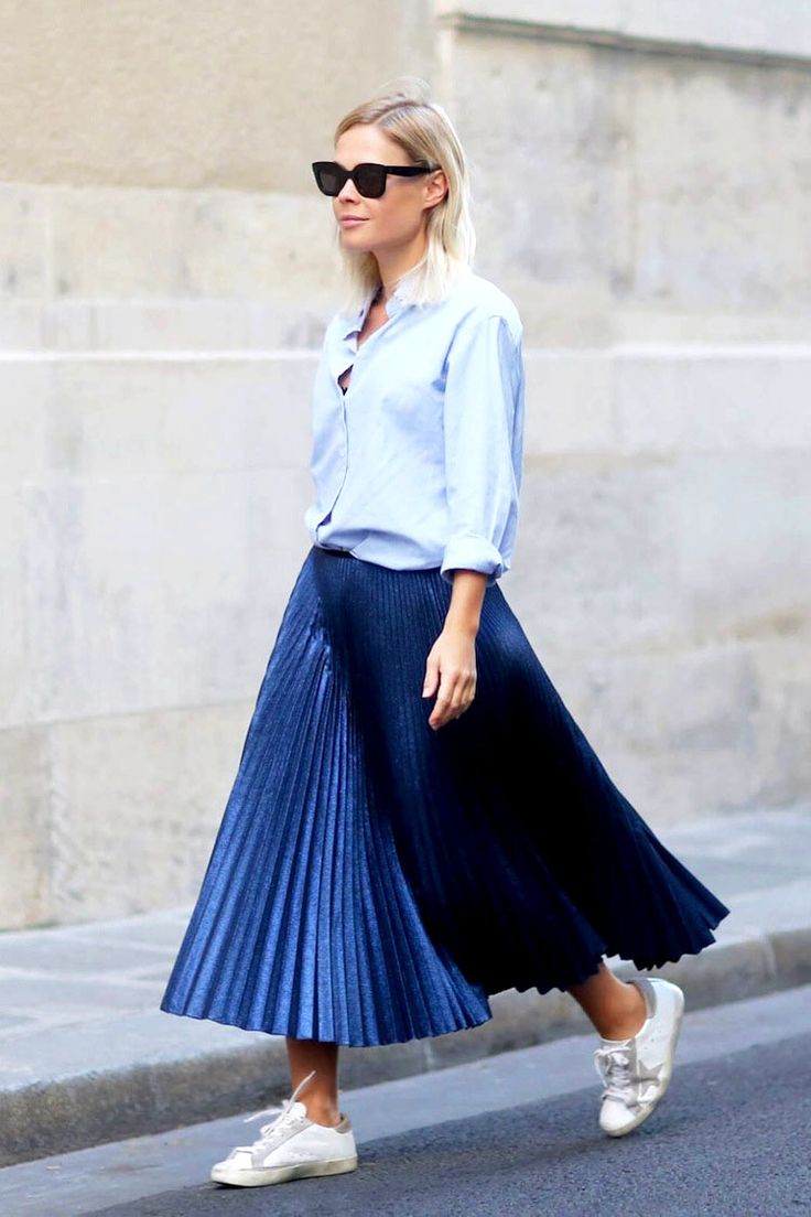 Jessie Bush shows three incredibly cool ways to wear a pleated midi skirt like this take with a classic blue button-down shirt and white sneakers.