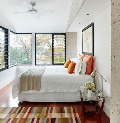 An earthy-toned stripy rug from Rugs Of The World in the UK complements the wide, grey ironbark flooring and warms up the Dulux Natural White walls. The bedside table, sanded and re-stained, is a legacy from the couple's university days.