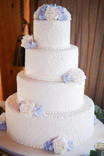 Weiße vierstöckige Hochzeitstorte mit unterschiedlichem Ornament auf …   – Hochzeitstorten