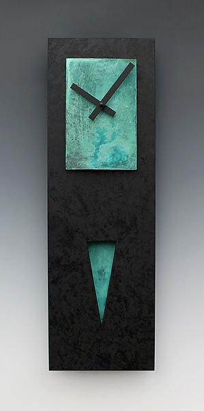 Verdigris Spike Pendulum Clock by Leonie Lacouette.  This wall clock has a black-on-black painted wooden background. The rectangular face and triangular pendulum are copper with a verdigris patina that ranges from gray-green to aquamarine. The pendulum swings behind a triangular cutout in the background. The perfect clock for a narrow space. Find it at www.artfulhome.com