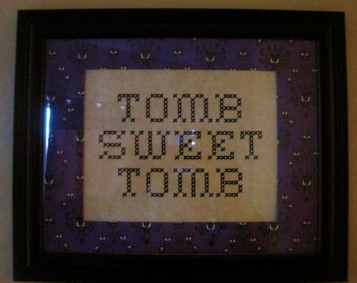 """""""This is hanging in my bathroom, I bought in on etsy here. It's inspired by a similar sign on a wall in the Haunted Mansion ride, but the colors are different. The original looks like a yellow and orange-faded cross-stitch, this one has the Haunted Mansion wallpaper border which I like better anyway."""""""