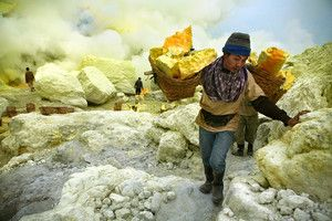 Ijen---Sulfur-miner-makes-the-climb-up-with-a-heavy-load.jpg-Kawah Ijen is Java's famous sulfur-belching volcanic crater. It is also the regular workplace for almost three hundred men, who make the grueling journey up the mountain and down the crater rim to mine sulfur.