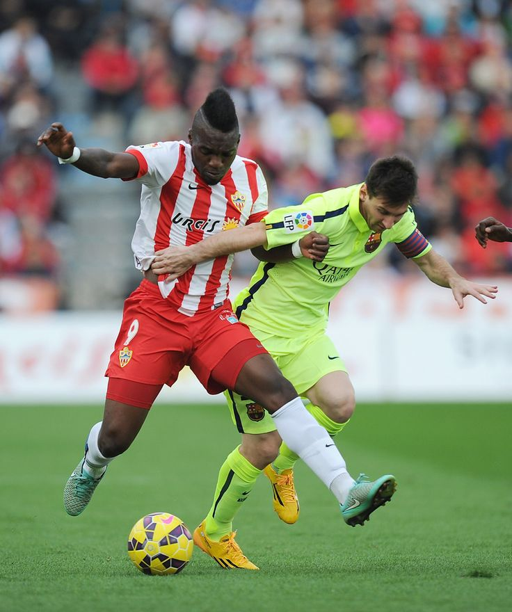 Thievy Guivane of UD Almeria tackles Lionel Messi of FC Barcelona during the La Liga match between UD Almeria and FC Barcelona at estadio de los Juegos Mediterraneos on November 8, 2014 in Almeria, Spain.