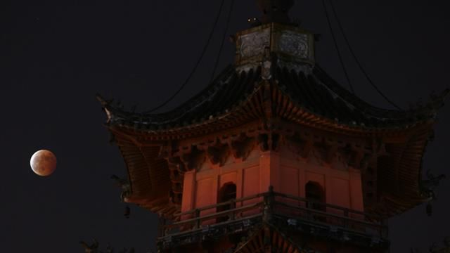 The Blood Moon October 2014. The glowing red moon behind a tower in Ningbo city, China. (AAP)