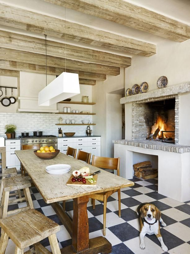 Mediterranean Style With Rustic Fireplace: A wood-burning fireplace designed for cooking adds Mediterranean charm to this eat-in kitchen. The communal farm table is the centerpiece of the space. A modern light fixture provides a foil for the rough-hewn ceiling beams. From HGTVRemodels.com
