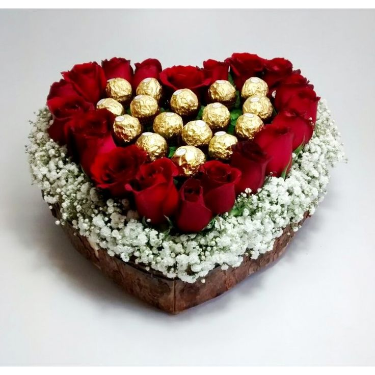 arreglo de rosas con chocolates en una base de corazon