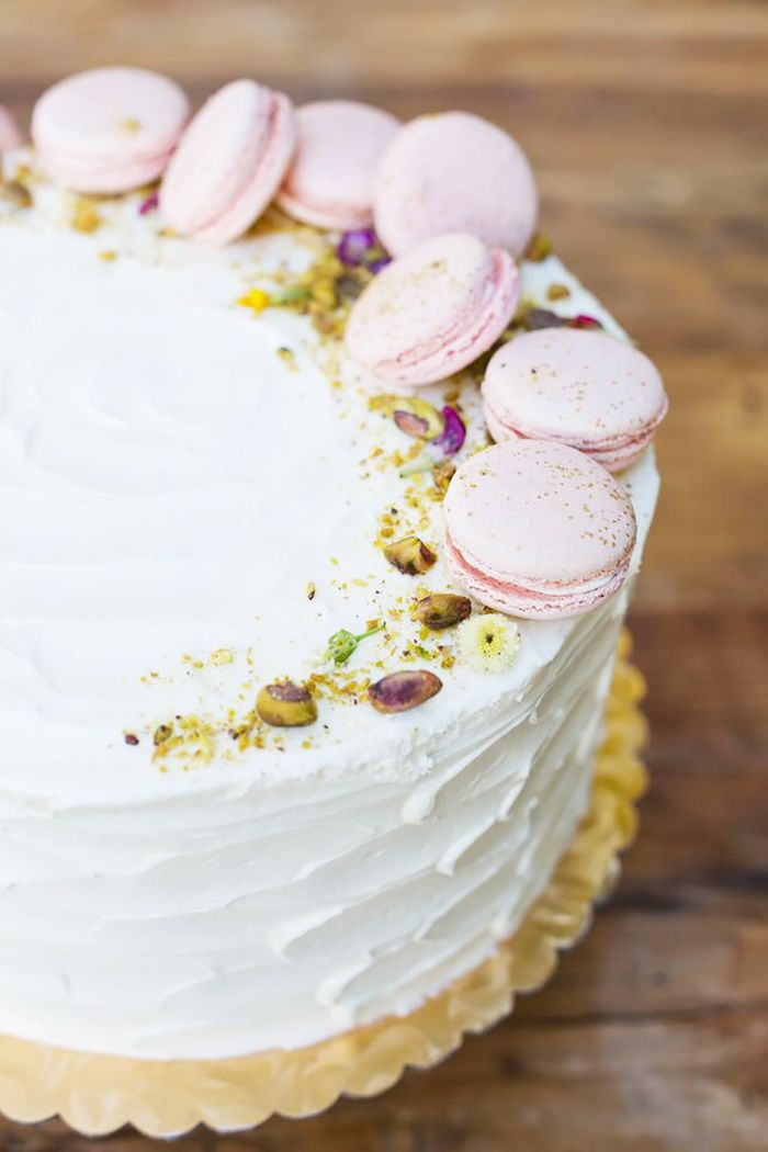 An iced white cake with pistachio pieces and macarons