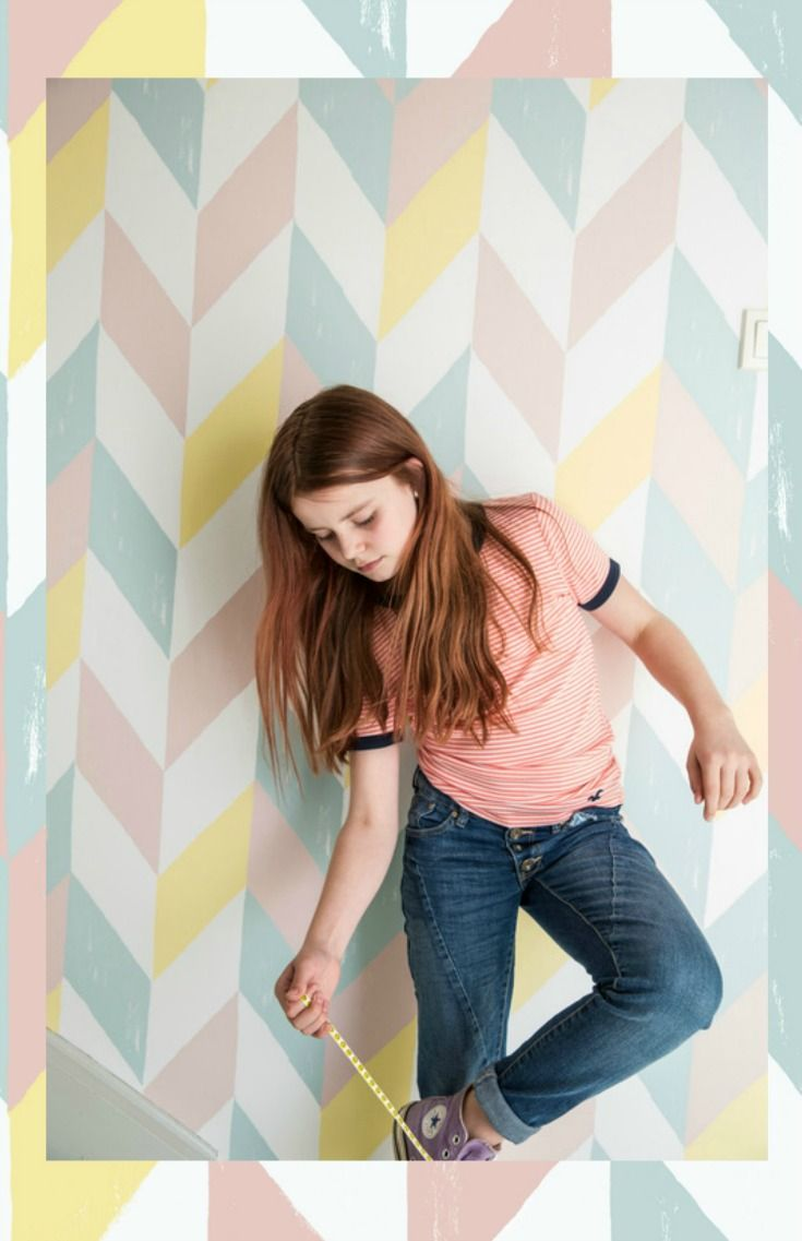 A large all over chevron wallpaper design in shaded tones of pink, duck egg, yellow and white.