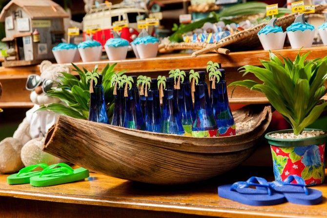 festa surf com garrafas de água decoradas. A utilização da chita nos detalhes deixou essa decoração de aniversário de menino ainda mais charmosa e colorida. Repare no ursinho com óculos de sol