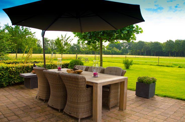 Tuinset met gevlochten tuinstoelen en een teakhouten tafel voor een landelijke tuin
