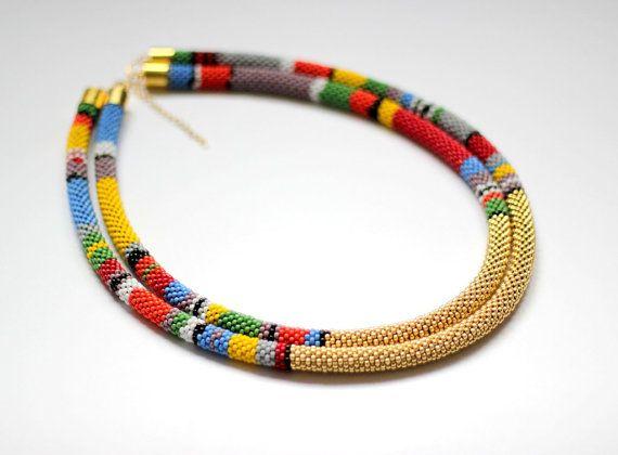 Totaal unieke, twee-strand, leyered ketting, geïnspireerd door Afrikaanse kralen sieraden, gemaakt in kraal haak techniek. Gouden secties in het midden van beide kleurrijk, gestreepte strengen geven een sfeer van elegantie toe aan het. Deze ketting zal indruk maken op degenen om je heen en maak die u zich van de menigte onderscheiden.  Zeer opvallende stuk van juwelen!  Materialen: Japanse beeds in zwart, rood, oranje, geel, grijs, lavendel, witte, zwarte, blauwe, groene en gouden kleuren…