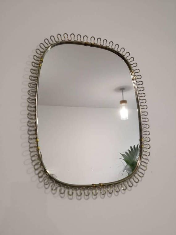 A very nice old wall mirror by Josef Frank for Svenskt Tenn in a great refined Midcentury design from the 1950s to the 1960s. A very high quality product with a long history.  With original back of wood and golden cord for hanging.  Size incl. frame: approx. 58 x 36 cm Size Mirror: