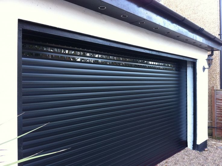 Insulated Gliderol roller garage doors installed with vision slats to allow light to enter the garage space. The black works very well in contrast to the cream building facade.