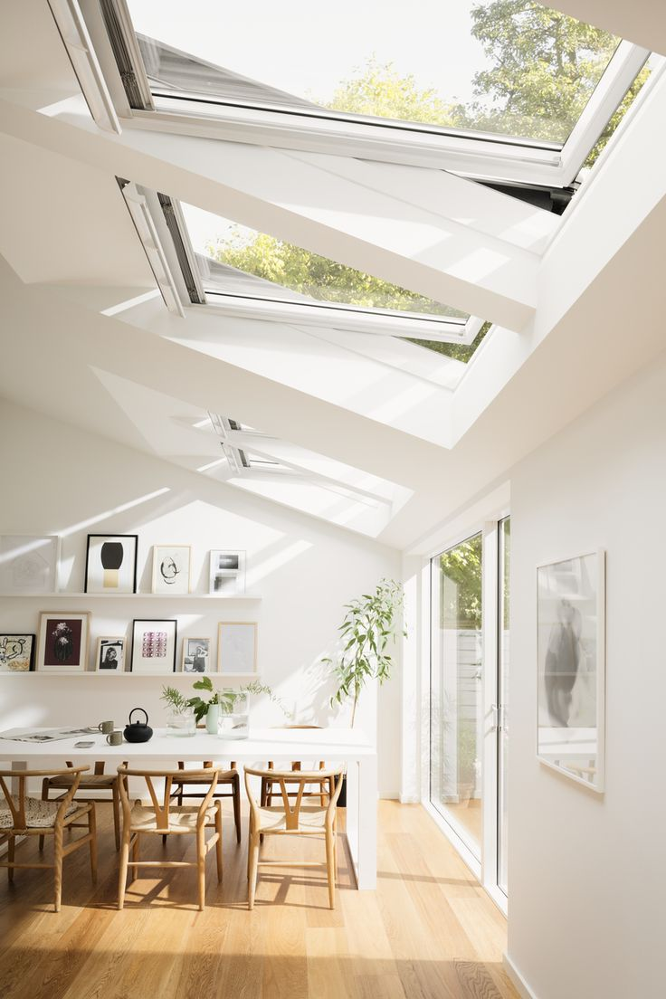Roof windows and increased natural light - Hege in France - white scandinavian dining room with wishbone chairs and a garden view. Natural light in abundance.