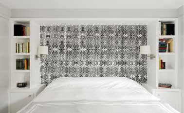 Dans une chambre blanche, la niche formée par les deux meubles colonnes était l'occasion rêvée de la tapisser pour en faire une tête de lit somme toute originale avec un papier peint aux motifs géométriques noirs et blancs. Une fantaisie qui rompt le côté monochrome de la chambre.