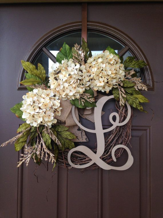 This lovely wreath will make a wonderful addition to your home decor or a thoughtful gift for a special person or occasion Beautiful wreath with 3 cream hydrangea blossoms surrounded by hydrangea leaves and additional greenery , accented with double burlap bow. Made on 18 grapevine wreath base, finished product measures approximately 19-20  in diameter.  Add monogram of your choice for a personal touch.Please make sure you specify your letter in the note when placing order :)  All our…