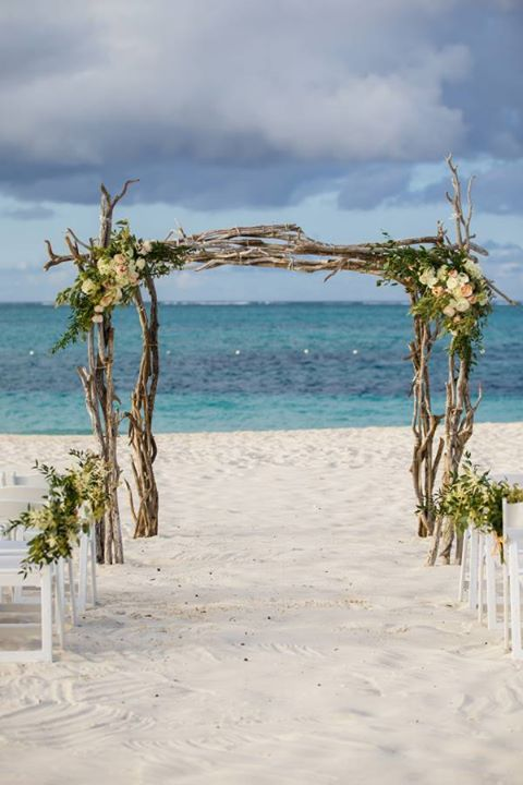 A rustic arch of pieces of wood with flowers is perfect for a beach wedding ~ http://www.stylemepretty.com/destination-weddings/turks-and-caicos/2016/02/27/romantic-turks-and-caicos-wedding/