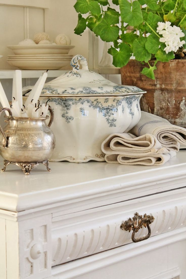 .love the mix of refined European porcelain and silver with the rustic terra cotta pot with geranium