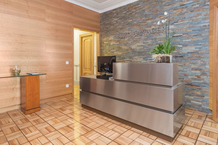 Reforma de recepción en oficina con diseño de mueble de recepción hecho a medida de acero inoxidable, empanelado de paredes con madera de cerezo y elaboración de pared con lajas de cuarcita