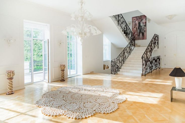 Magnificent in its size and its beauty. This handcrafted carpet is bringing loveliness to a family villas living room. Complimenting the beautiful wooden flooring. Funky contrast with the metal staircase. Design carpet by Merle Holm