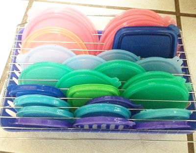 Attach a cooling rack to the top of a basket to organize all of those pesky food storage lids. Just thread fishing line through the holes in the basket and over the top of the drying rack to hold it in place.