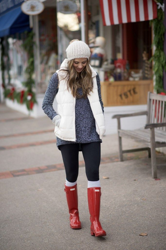 Cozy casual mom outfit with red Hunter boots, leggings, an oversized sweater, and puffy vest.
