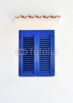 Finestra chiusa con persiane blu su muro bianco