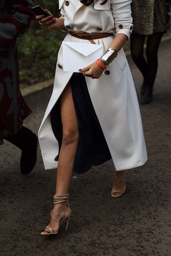 White trench, high slit black skirt, woven brown belt and neutral high heel sandals