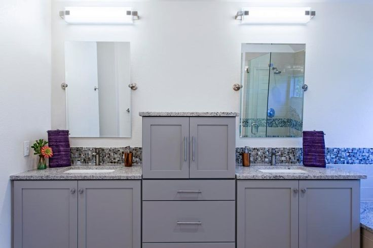 A raised linen cabinet allows for increased storage space and provides separate vanities in this serene, transitional bathroom. By strategically planning electrical access in the linen storage, the homeowners are able to charge and store their bathroom accessories while keeping their counter space free from clutter.